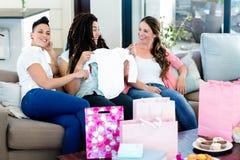Trois femmes s'asseyant sur le sofa et regardant des vêtements de babys Photos stock
