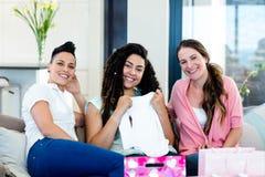Trois femmes s'asseyant sur le sofa et regardant des vêtements de babys Images libres de droits