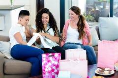 Trois femmes s'asseyant sur le sofa et regardant des vêtements de babys Photographie stock libre de droits