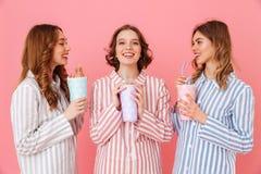 Trois femmes satisfaites avec bonne humeur dans des pyjamas rayés colorés s Image libre de droits