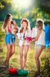 Trois femmes avec les équipements provocateurs mettant des vêtements pour sécher en soleil Jeunes femelles sensuelles riant  Photos stock