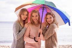 Trois femmes sous le parapluie coloré Image stock