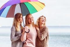 Trois femmes sous le parapluie coloré Images stock