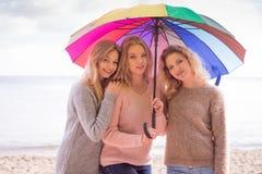 Trois femmes sous le parapluie coloré Photographie stock libre de droits