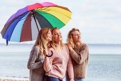 Trois femmes sous le parapluie coloré Photographie stock