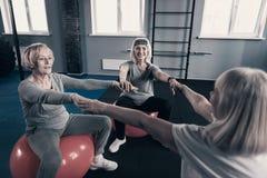 Trois femmes supérieures sur des boules de stabilité tenant des mains Photographie stock libre de droits