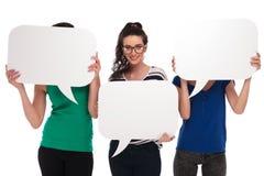 Trois femmes tenant la parole bouillonne, deux visages de couvert Photos libres de droits