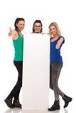 Trois femmes tenant un panneau d'affichage et font le signe correct Photos libres de droits