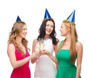 Trois femmes utilisant des chapeaux avec des verres de champagne Photo stock