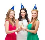 Trois femmes utilisant des chapeaux avec des verres de champagne Photographie stock