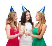 Trois femmes utilisant des chapeaux avec des verres de champagne Image stock