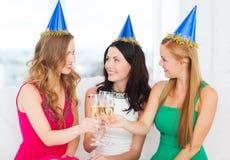 Trois femmes utilisant des chapeaux avec des verres de champagne Photographie stock libre de droits