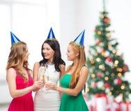 Trois femmes utilisant des chapeaux avec des verres de champagne Images libres de droits
