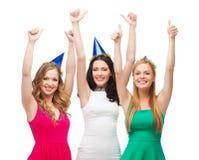 Trois femmes utilisant des chapeaux et montrant des pouces  Photos libres de droits