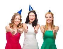 Trois femmes utilisant des chapeaux et montrant des pouces  Photographie stock libre de droits