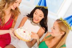 Trois femmes utilisant des chapeaux tenant le gâteau avec des bougies Photo libre de droits