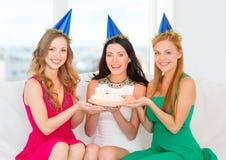 Trois femmes utilisant des chapeaux tenant le gâteau avec des bougies Photos libres de droits