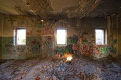 Trois fenêtres cassées d'un vieux bâtiment abandonné Photographie stock libre de droits