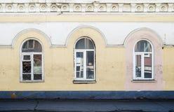 Trois fenêtres d'un bâtiment antique Fragment de la façade Photographie stock libre de droits
