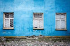 Trois fenêtres sur un mur bleu Image libre de droits