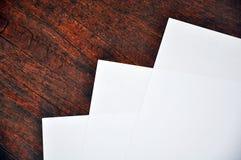 Trois feuilles de livre blanc se trouvant sur une surface en bois Images stock