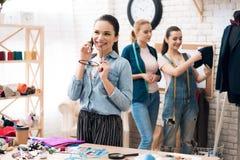 Trois filles à l'usine de vêtement desining la nouvelle veste de costume avec l'un d'entre eux parlant au téléphone image stock