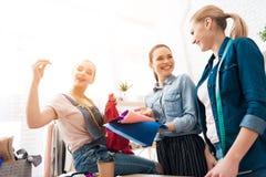 Trois filles à l'usine de vêtement Ils choisissent le tissu pour la nouvelle robe et une fille coud image stock