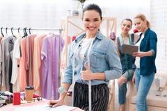 Trois filles à l'usine de vêtement Ils regardent le comprimé et l'un d'entre eux avec la bande de mesure Photo stock