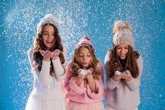Trois filles à la mode en hiver ont tricoté l'hiver de neige de chapeaux images libres de droits