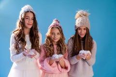 Trois filles à la mode en hiver ont tricoté l'hiver de neige de chapeaux photographie stock