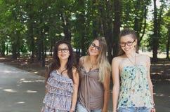 Trois filles élégantes chics de beau jeune boho marchant en parc photographie stock