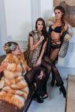 Trois filles attirantes dans la lingerie sexy et des manteaux de fourrure de luxe posant dans l'intérieur moderne Photo libre de droits