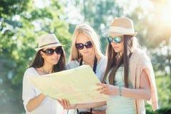 Trois filles attirantes recherchant des directions sur une carte aux vacances d'été Image libre de droits