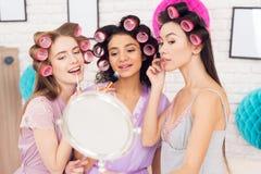 Trois filles avec des bigoudis dans leur faire de cheveux composent derrière le miroir Ils célèbrent des femmes ` s jour le 8 mar Image stock