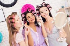 Trois filles avec des bigoudis dans leur faire de cheveux composent derrière le miroir Ils célèbrent des femmes ` s jour le 8 mar Photographie stock