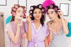 Trois filles avec des bigoudis dans leur faire de cheveux composent Ils célèbrent des femmes ` s jour le 8 mars Photos stock