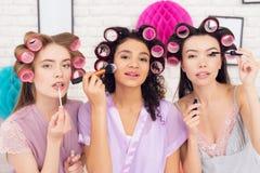 Trois filles avec des bigoudis dans leur faire de cheveux composent Ils célèbrent des femmes ` s jour le 8 mars Images stock