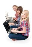 Trois filles avec des ordinateurs portatifs Photo stock