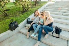 Trois filles ayant l'amusement dans le parc de coucher du soleil Image stock