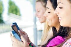 Trois filles causant avec leurs smartphones Photo libre de droits
