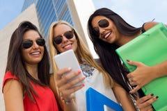 Trois filles causant avec leurs smartphones au campus Photos libres de droits