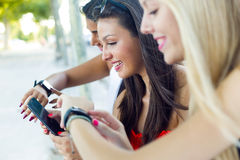 Trois filles causant avec leurs smartphones au parc Photos libres de droits