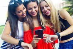 Trois filles causant avec leurs smartphones au parc Photographie stock