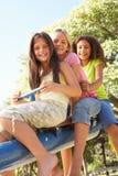 Trois filles conduisant sur la balançoir dans la cour de jeu Image libre de droits