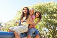 Trois filles conduisant sur la balançoir dans la cour de jeu Photographie stock