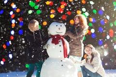 Trois filles construisant un bonhomme de neige Photos libres de droits