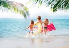 Trois filles courant en mer à la plage tropicale Photographie stock libre de droits
