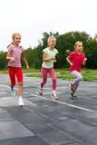 Trois filles courues vers le bas autour du stade Images stock