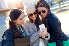 Trois filles d'étudiants à l'aide du téléphone portable dans le campus Photographie stock libre de droits