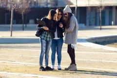 Trois filles d'étudiants à l'aide du téléphone portable dans le campus Photographie stock